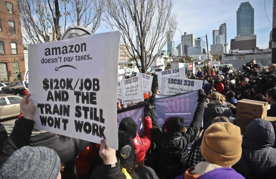 protester at Amazon protest holding sign that says Amazon doesn't pay taxes and our subways still won't work.