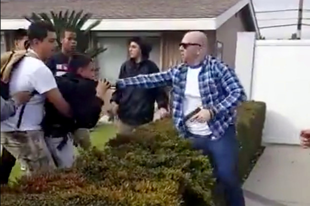 LAPD Officer Kevin Ferguson grabs a minor while holding a gun